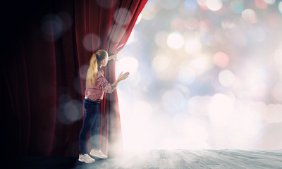 Girl opening curtain