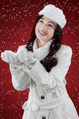 Cute woman catching snowfall