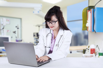 Doctor working on laptop in hospital