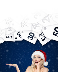 Beautiful woman in Christmas cap gestures palm up offer