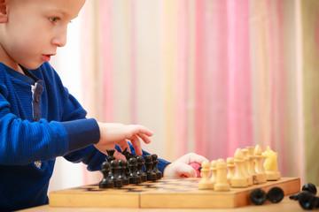 Childhood. Intelligent boy child kid playing chess. At home.