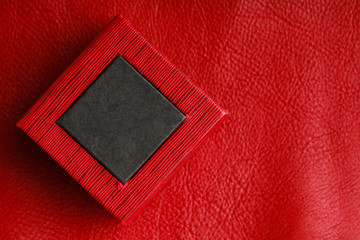 Red black rectangular ring box on leather background