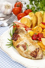 Joint of pork with baked potatoes and fresh vegetables