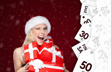 Pretty woman in Christmas cap holds a set of presents from sale