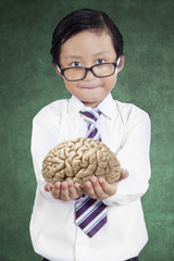 Little businessman holds brain