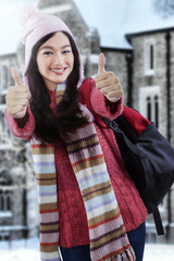 Student in sweater giving thumbs-up