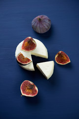 Above view of sliced cheese and figs, vertical shot