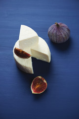 Sliced cheese and fig fruits over dark blue wooden surface