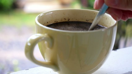 Hand Stirring Steaming Cup of Black Coffee.