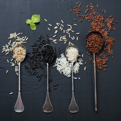 Variety of raw rice in vintage spoons, close-up, view from above