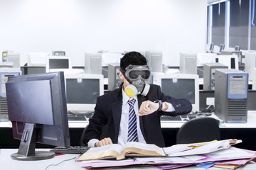 Worker with gas mask in office