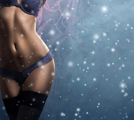 Sexy body of a woman in luxury lingerie on a snowy background