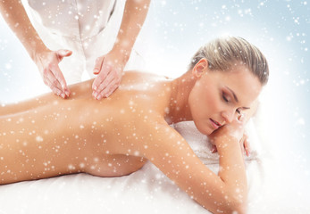 Young woman getting spa treatment on a snowy background