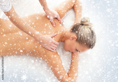 Young woman getting spa treatment on a snowy background - 73558327