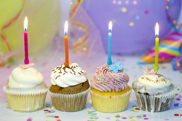 Birthday cupcake closeup on colorful background with candle