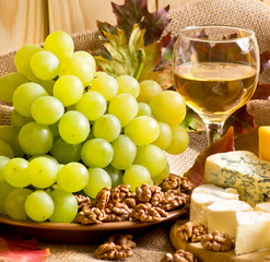 White wine with cheese, walnuts and grapes on sackcloth