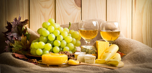 White wine with cheese, honey, walnuts and grapes on sackcloth