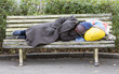 Homeless man sleeping on a bench - 73560121