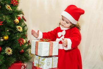 Маленькая девочка играет с подарками под елкой