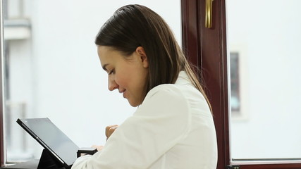 Woman using tablet computer and smart watch in the office