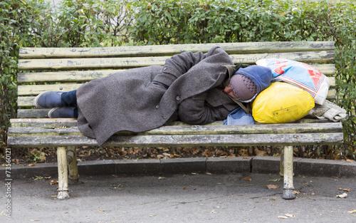 Leinwanddruck Bild Homeless man sleeping on a bench