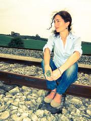Woman sitting on a rail track