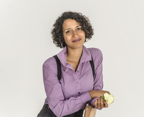 Young mulatto woman in a business suit eat apple