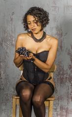 Beautiful woman in lingerie mulatto eat fruit