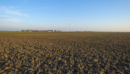 Wind farm along a plowed field at sunset in autumn