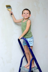 A boy stands on a ladder with a brush in his hand