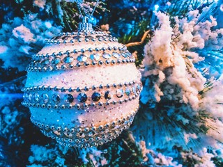Christmas ball decoration on fir tree with snow