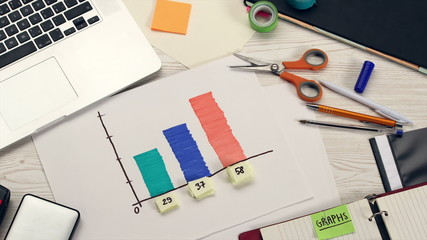 Creating graph on office desk, stop motion animation, top view