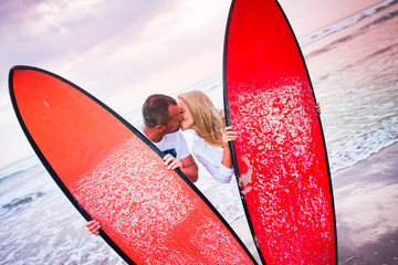 Couple of surfers kissing on coast in Indonesia
