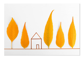 Autumn leaves with painted house on white background