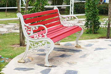 red steel bench with white armrest in garden