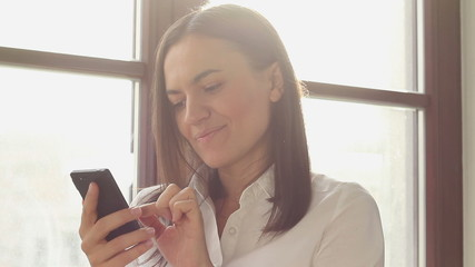 Businesswoman sending messages with her mobile phone, close up