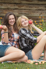 Blonde and brunette holding ripe apples