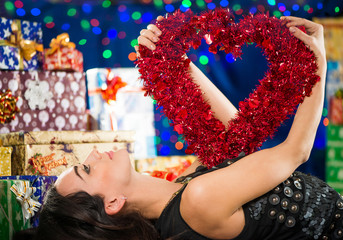 woman laying with red heat at holiday gifts background