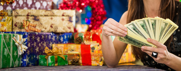 woman counting money at holiday gifts background