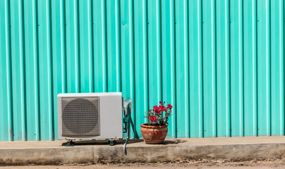 Old compressor air-conditioner and Flower Pot on zinc wall