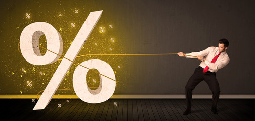Business man pulling rope with big procent symbol sign