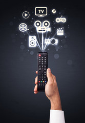 Hand with remote control and media icons