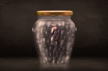 Business man trapped in jar with exclamation marks concept