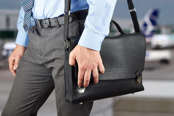 Businessman walking and holding  a  leather briefcase in his han