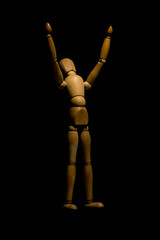 Wooden mannequin raising hands to light isolated on black.