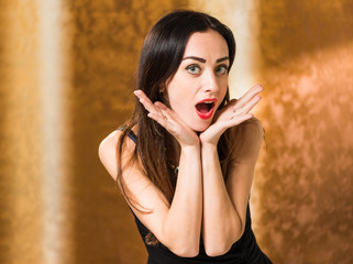 surprised woman portrait at golden background