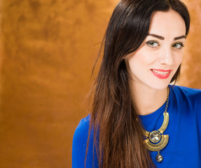 smiling lady in blue dress at golden background
