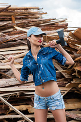 fashionable woman in jeans clothes ax in hand
