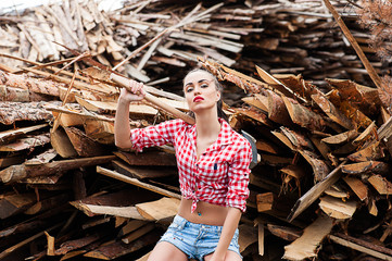 woman ax in hand in a plaid shirt sitting on wooden boards