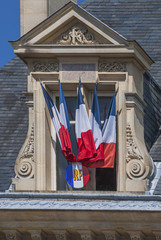 French flags in the window of Reims City Hall